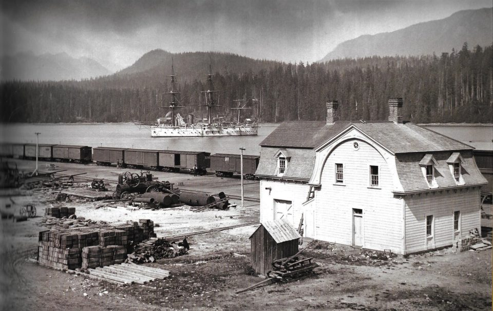 First CPR Port Moody station in Burrard Inlet, with British Man-of-war HMS Triumph anchored offshore, Summer 1886